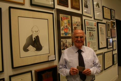 "Harold holds his press credential (circa 1940s) in front of his ""Wall of Narcissism."""